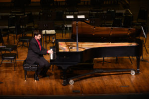 Dr. Geoffrey Pope demonstrates on the piano during his pre-concert lecture.